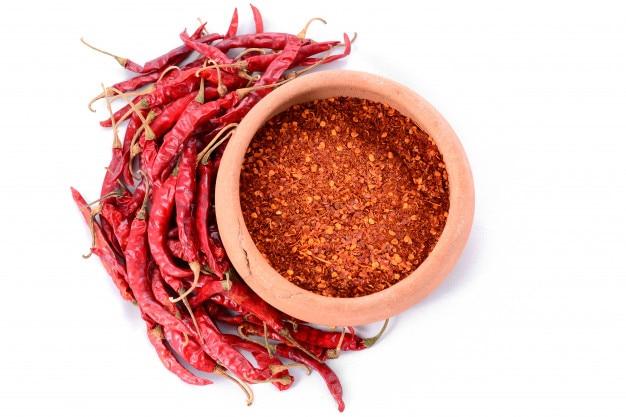 Rode spaanse pepers met rood koud poeder op witte achtergrond