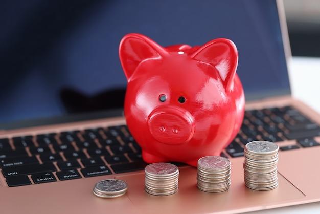 Rode spaarvarken en muntstukken op laptop toetsenbord. snel geld online concept