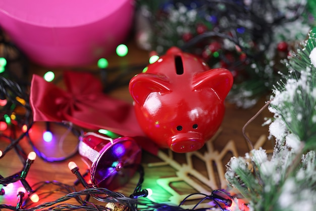 Rode spaarvarken staande in de buurt van kerstcadeaus en klatergoud close-up