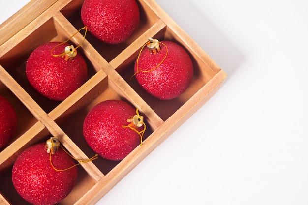 Rode sparkle kerstballen in een houten doos.