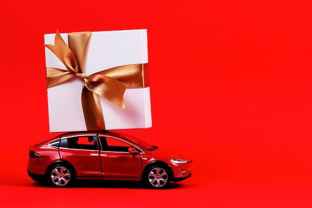 Rode speelgoed modelauto met huidige geschenkdoos op de bovenkant op rood
