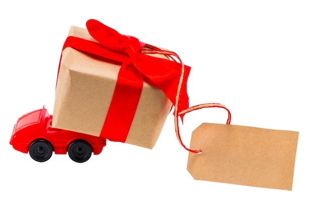 Rode speelgoedauto die een geschenkdoos levert met een label met lege ruimte voor een tekst op een witte achtergrond.