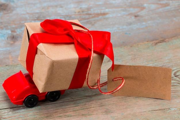 Rode speelgoedauto die een geschenkdoos levert met een tag met lege ruimte voor een tekst op een houten ondergrond.
