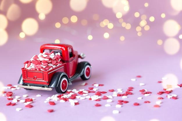 Rode speelgoedauto met een geschenkdoos op het dak op een roze muur voor valentijnsdag muur.