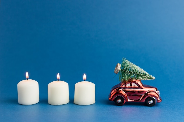 Rode speelgoedauto met een kerstboom op het dak en kaarsen