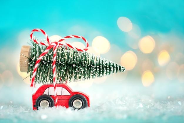 Rode speelgoedauto met een kerstboom op het dak op een bokeh feestelijke blauwe achtergrond. kerstmis en nieuwjaar concept