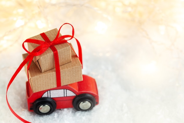 Rode speelgoedauto met stapel kerst geschenkdozen