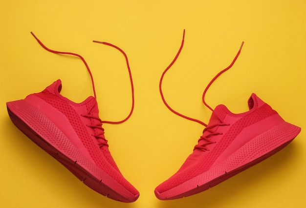 Rode sportloopschoenen met ongebonden veters op gele achtergrond