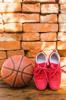 Rode sportschoenen en basketbal tegen stapel van bakstenen muur