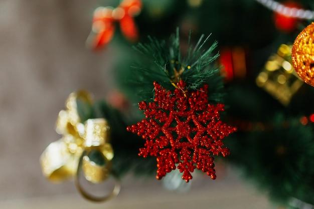 Rode ster opknoping van een versierde kerstboom met gouden bogen en ballen. selectieve aandacht. detailopname.