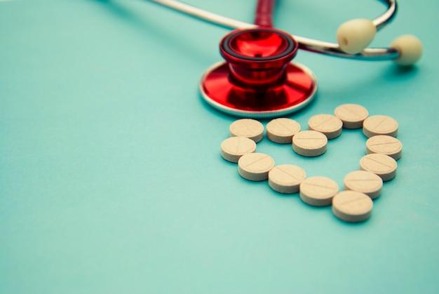 Rode stethoscoop met tabletten, pillen op blauw. copyspace. geneeskunde, heartbeast.