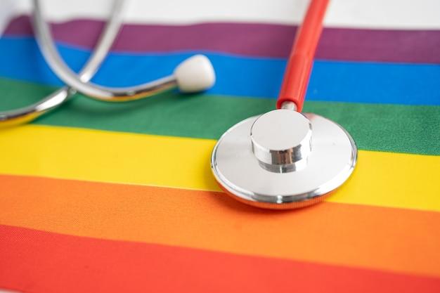 Rode stethoscoop op het symbool van de regenboogvlag als achtergrond van lgbt-trotsmaand