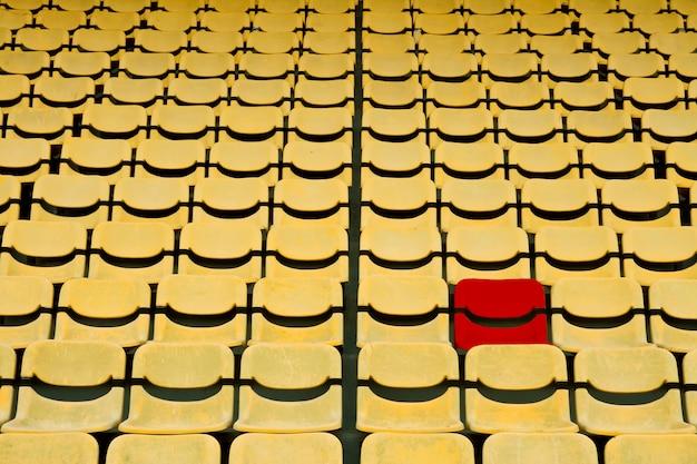 Rode stoel in geel zitvlakpatroon in voetbalstadion