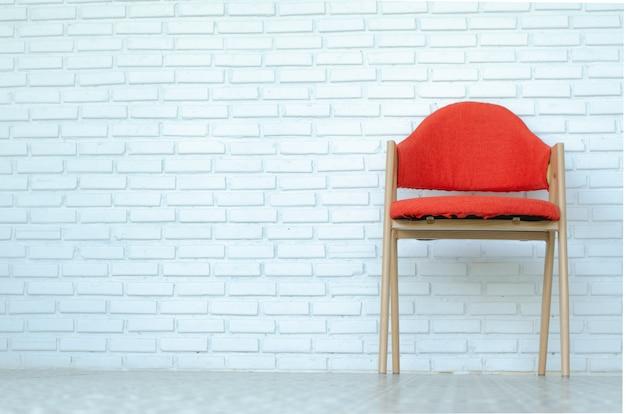Rode stoel op witte baksteenachtergrond, moderne ruimte, exemplaarruimte.