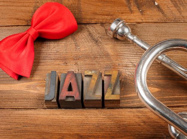 Rode strik en zilveren trompet op hout en woordjazz in letterzetseltype