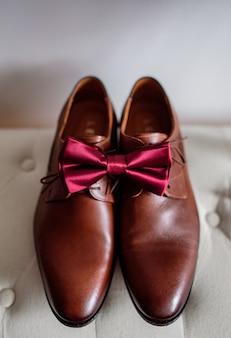 Rode strikje ligt op bruin lederen schoenen
