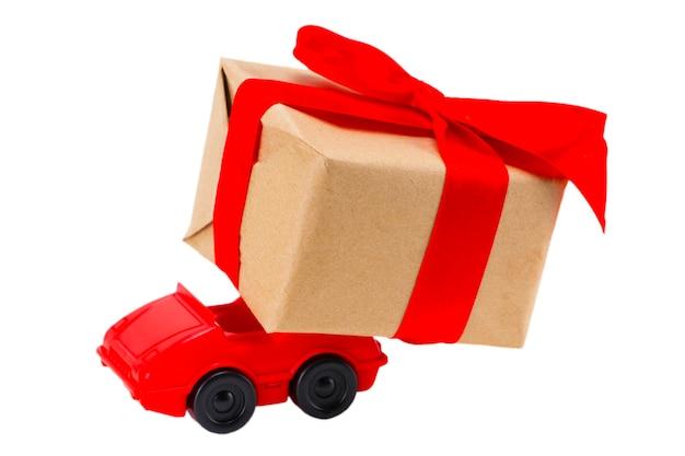 Rode stuk speelgoed auto die giftendoos op een witte achtergrond levert.