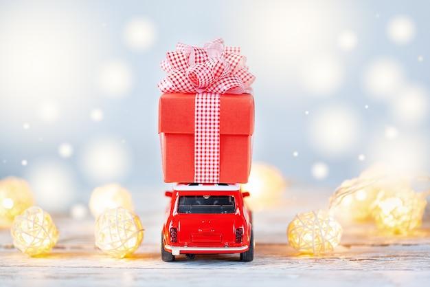 Rode stuk speelgoed auto die op dak een rode giftdoos op blauwe achtergrond draagt