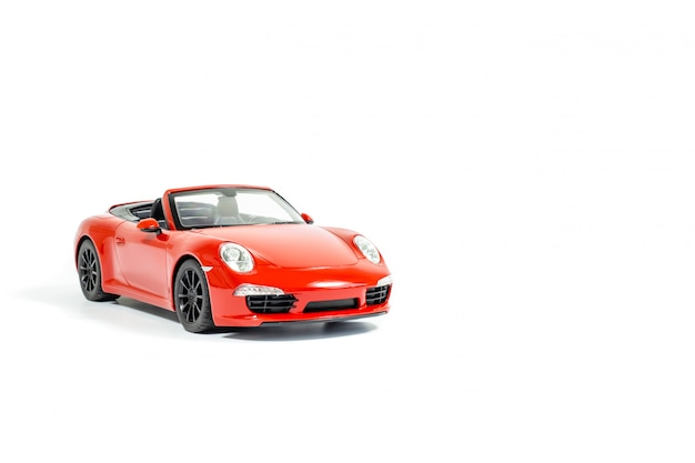 Rode stuk speelgoed auto, die op witte achtergrond wordt geïsoleerd