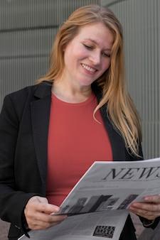 Rode t-shirtkleding plus size zakenvrouw die de krant leest