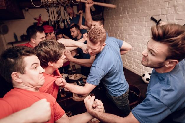 Rode teamhooliganfans en blauwe teamhooligan.