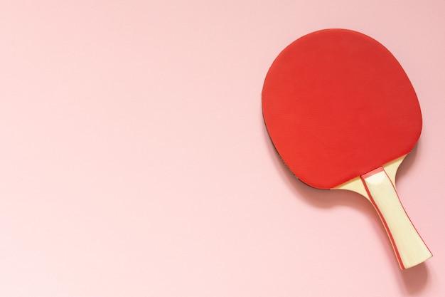 Rode tennis ping pong racket geïsoleerd op een roze achtergrond, sportartikelen voor tafeltennis