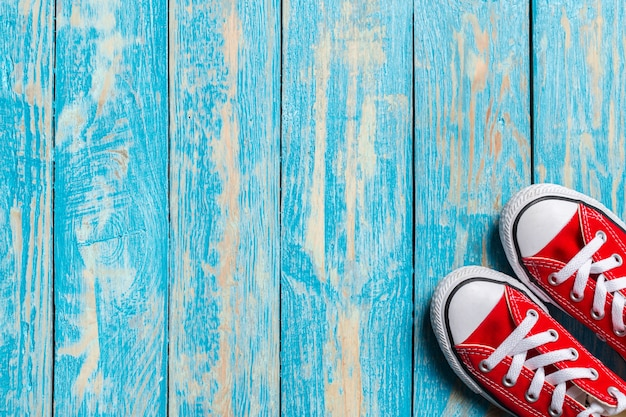 Rode tennisschoenen op houten achtergrond.
