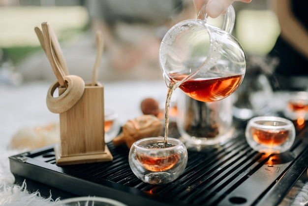 Rode thee in een glazen theepot wordt in kopjes gegoten. theeceremonie in het park in de ochtend