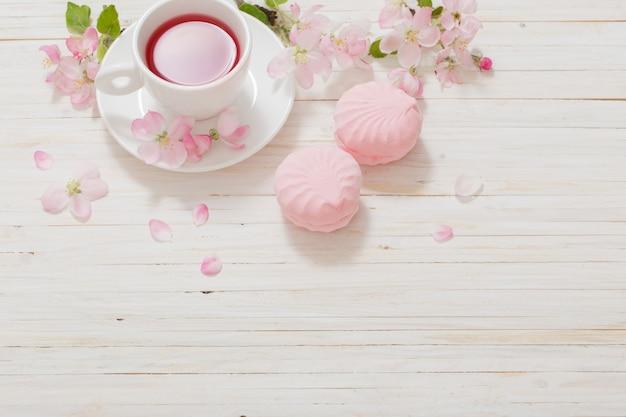Rode thee met bloemen op witte houten achtergrond
