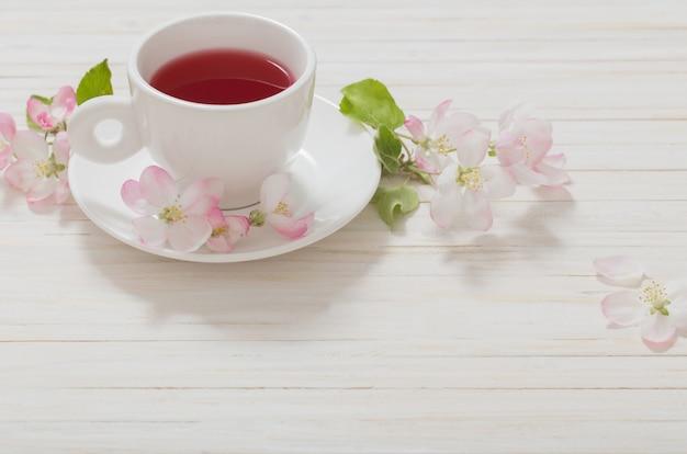 Rode thee met bloemen op witte houten ruimte