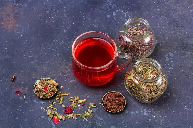 Rode thee (rooibos, hibiscus, karkade) in glazen beker en potten droge theebladeren en bloemblaadjes op donkere achtergrond. kruiden-, vitamine-, detoxthee voor verkoudheid en griep