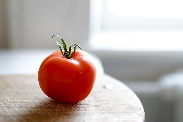 Rode tomaat op een scherpe houten raad op witte achtergrond.