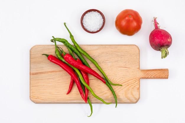 Rode tomaat, radijs, rode en groene chili pepers met houten snijplank