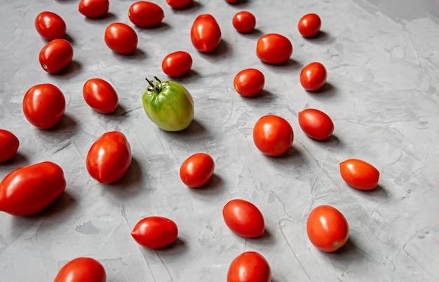 Rode tomaten en een groene tomaat op een grijze achtergrond
