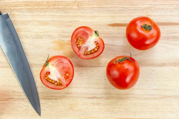 Rode tomaten en plakjes op houten snijplank