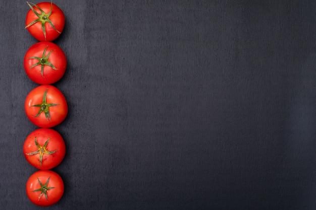 Rode tomaten gerangschikt aan de linkerkant met kopie ruimte