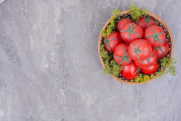 Rode tomaten in een houten schotel op het marmer