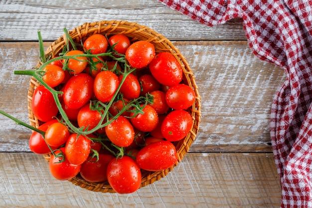 Rode tomaten in een rieten mand op houten en keukenhanddoek. plat lag.