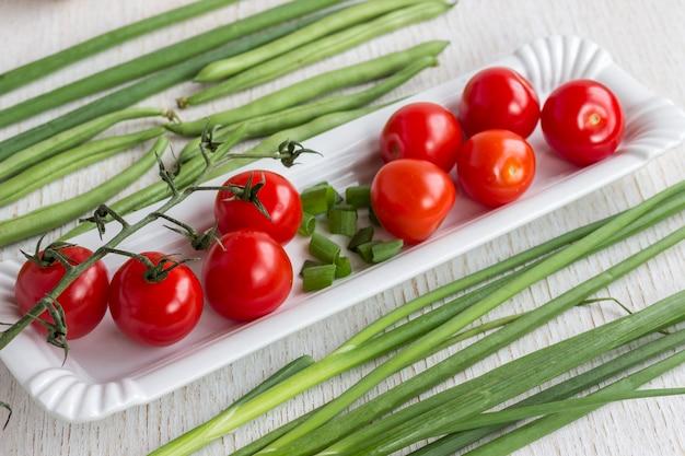 Rode tomaten in een witte plaat. uien en asperges op wit
