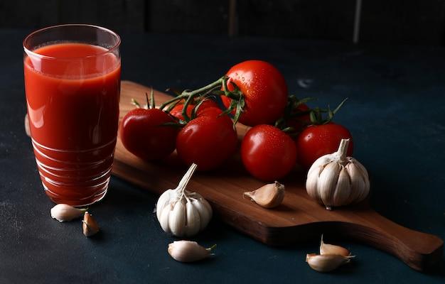 Rode tomaten, knoflookhandschoenen en een glas tomatensap.