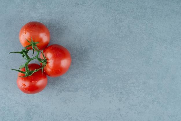 Rode tomaten met waterdruppels op blauw.