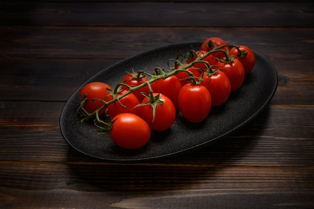 Rode tomaten op een groene tak op een donkere schotel op een houten achtergrond.