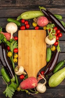 Rode tomaten verse en rijpe andere groenten zoals rode radijs en zwarte aubergines op een houten rustieke vloer