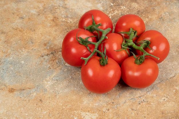 Rode tomatenkers op een tak op marmeren oppervlak.