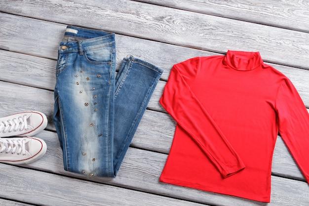 Rode top en blauwe spijkerbroek. casual denim broek en schoenen. kleding en schoeisel op showcase. kortingsactie is gestart.