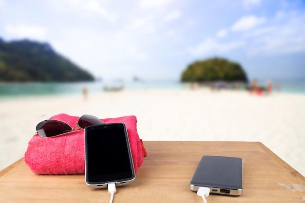 Rode toren, zonnebril, mobiel opladen met krachtbank over houten tafel op onduidelijk strandzand en blauwe hemelachtergrond.