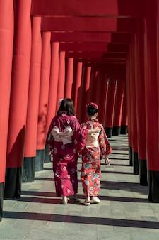 Rode torii-poorten met vrouw in kimono op hinoki-land oriëntatiepunt in chaiprakarn, chiang mai, thailand