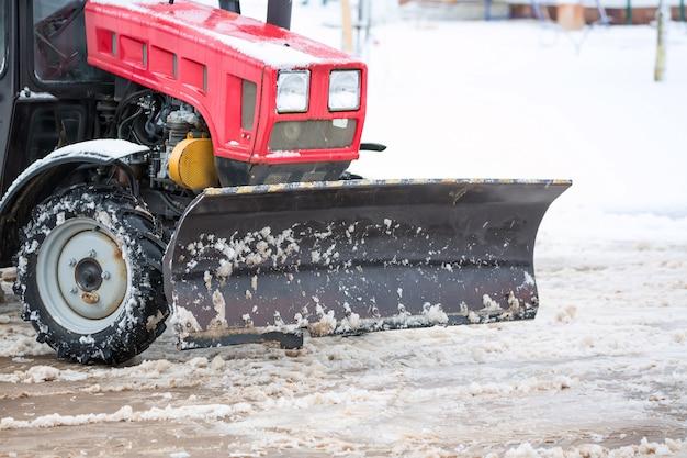 Rode tractor die de straten van grote hoeveelheden sneeuw in stad na sneeuwval schoonmaakt. wintertijd concept.