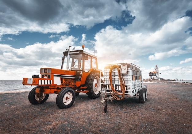 Rode tractor met aanhangwagen tegen vuurtoren en bewolkte hemel