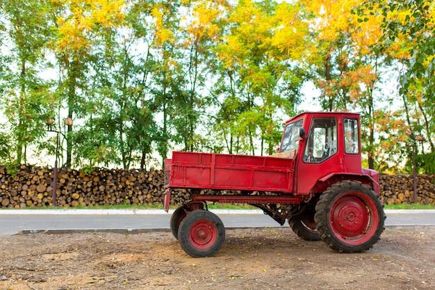Rode tractor met een boomstam vooraan.